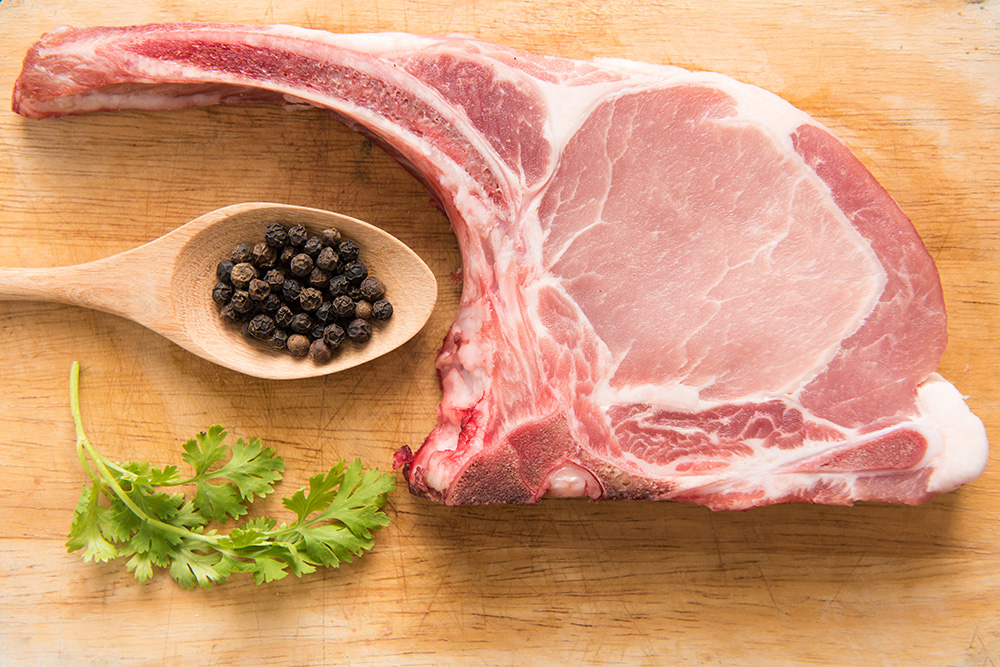 Fresh Raw Pork Chops and pepper in spoon on wooden background